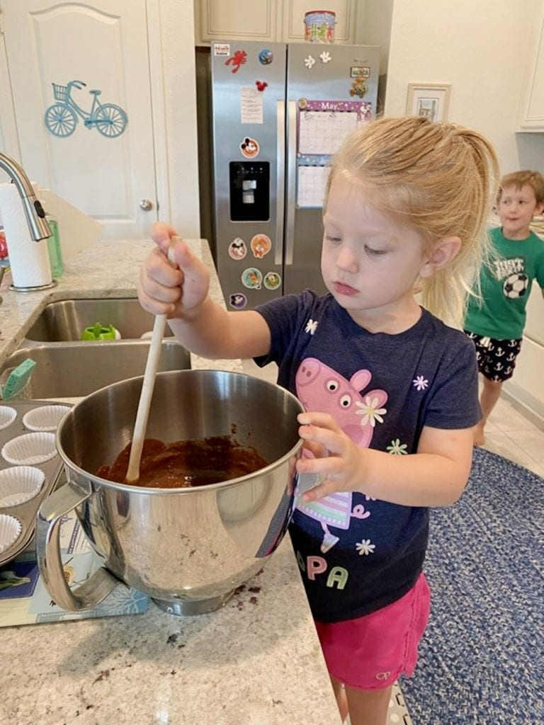 little girl making cupcakes